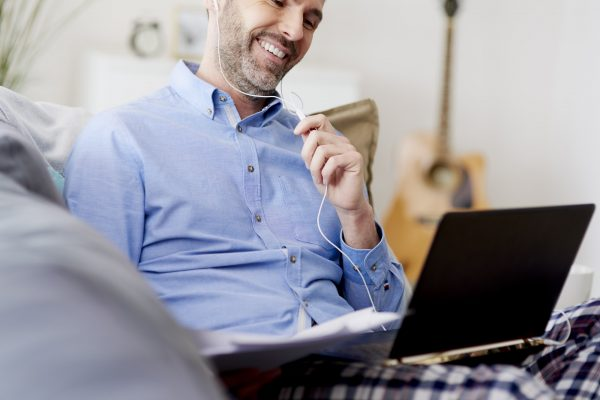 Cheerful man working home on the lapto