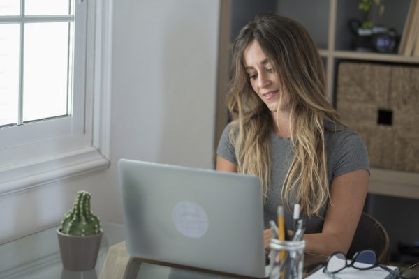 Happy adult Caucasian woman in professional look at laptop screen work online on laptop