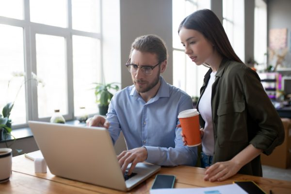 Serious man and girl looking together at a laptop.